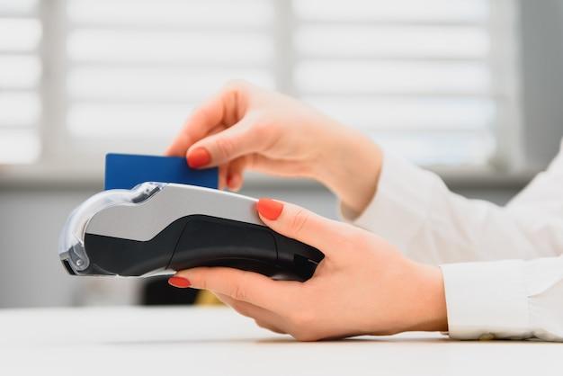Рука с кредитной картой проводит через терминал для продажи в супермаркете