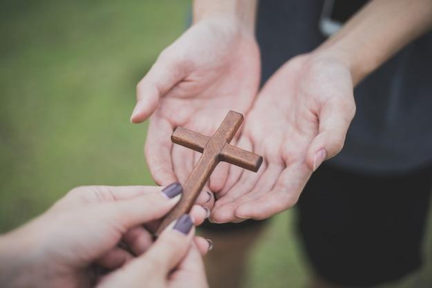 十字架で手。希望、信仰、キリスト教、宗教、教会の概念をオンラインで。