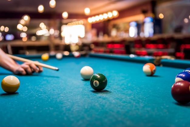 테이블에서 당구 공을 목표로 큐와 손