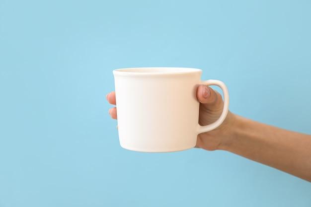 色の表面にカップを持って手