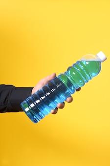 Рука с бутылкой моющего средства на желтом фоне