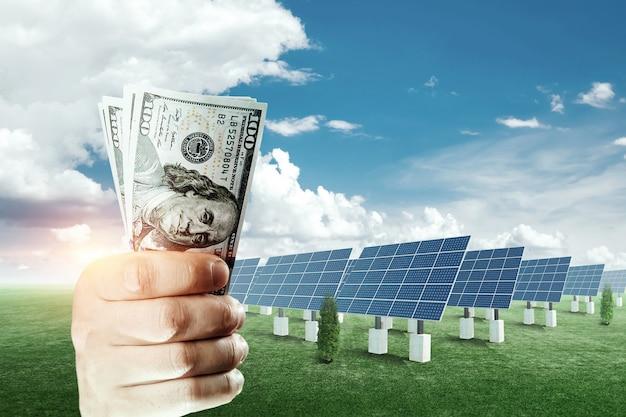태양 전지 패널의 배경에 달러와 손.. 태양 에너지 사업, 녹색 비용