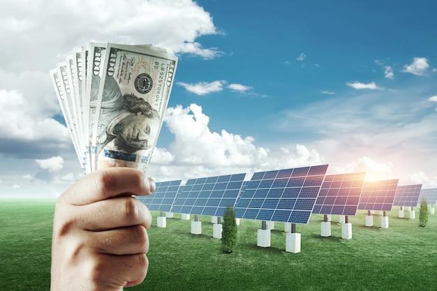 태양 전지 패널의 배경에 달러와 손. 태양 전지 패널 비용, 태양열 발전 사업입니다.