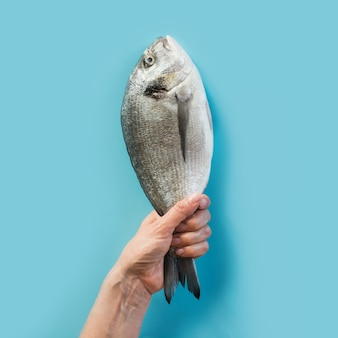 Hand with dorado fish