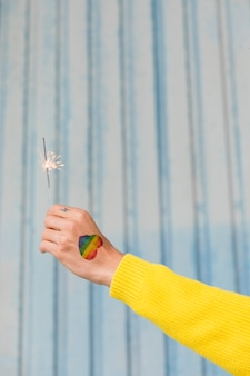 Hand with drawn rainbow heart holding burning sparkler