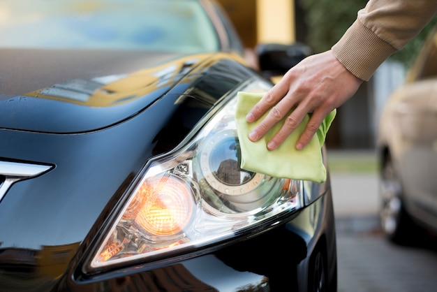 Hand with duster cleaning headlight of dark auto