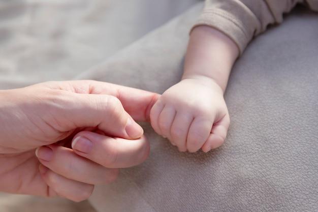 生まれたばかりの赤ちゃんとお母さんの手の指で手。