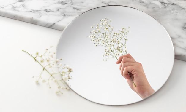 鏡に花を持って手