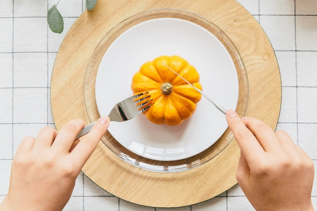 Hand with fork and knife cutting yellow pumpkin on white plate