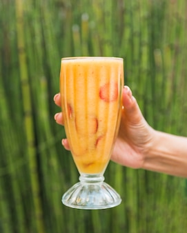 Hand with glass of fresh smoothie near bamboo