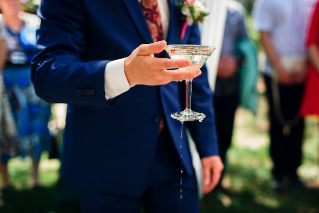 Hand with a glass of martini in the hand of the groom at the wedding