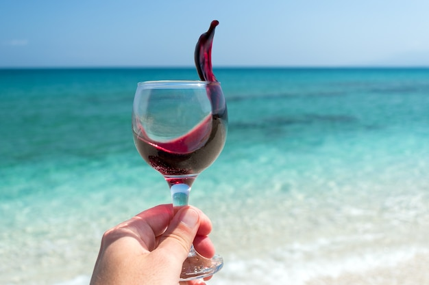 Рука с бокалом красного вина на пляже в летний солнечный день