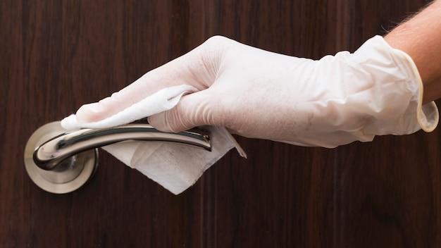 Рука с перчаткой для дезинфекции дверной ручки