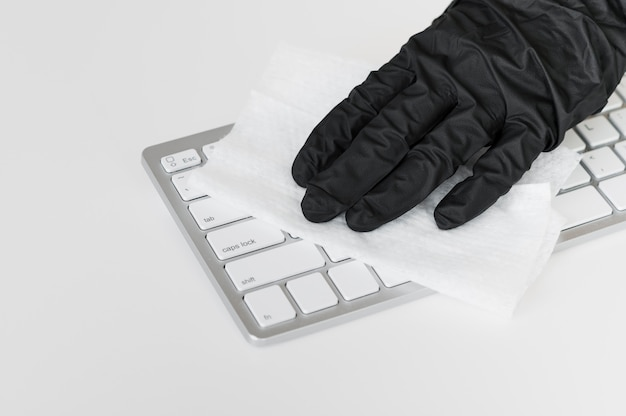 Hand with glove disinfecting keyboard surface