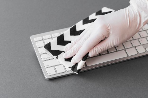Hand with glove disinfecting keyboard