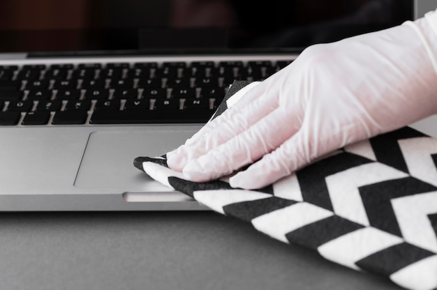 Hand with glove disinfecting laptop surface