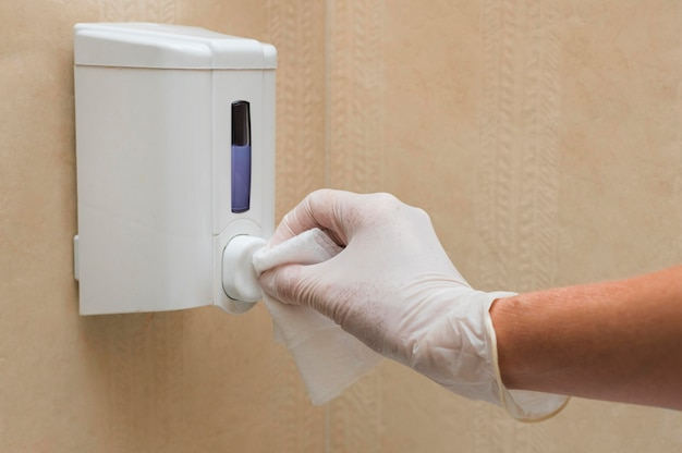 Hand with glove disinfecting soap dispenser