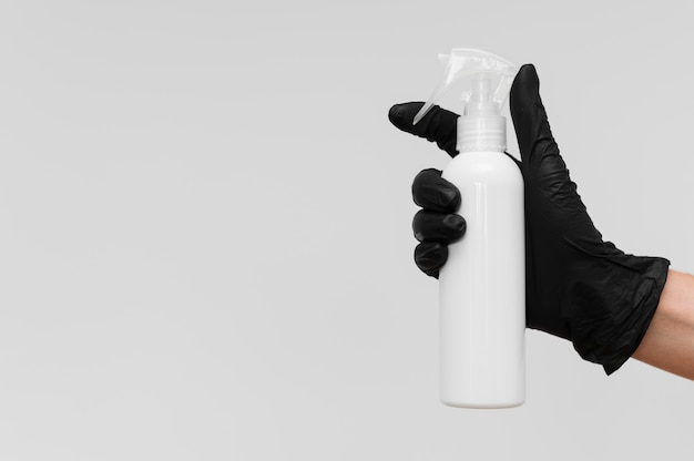 Hand with glove holding bottle of cleaning solution with copy space