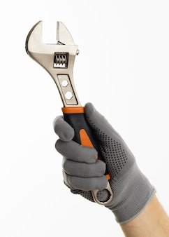 Hand with glove holding wrench