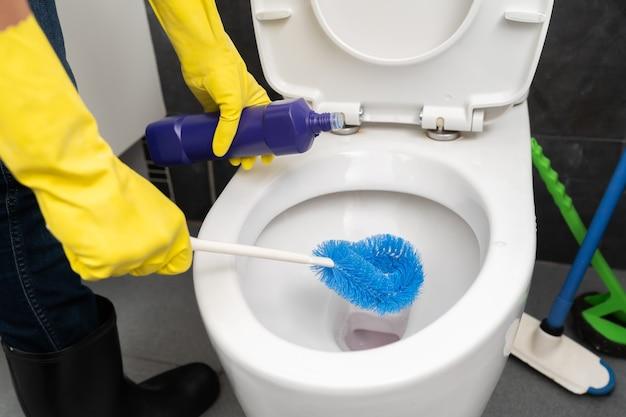 手袋をして手でトイレの便器を掃除する