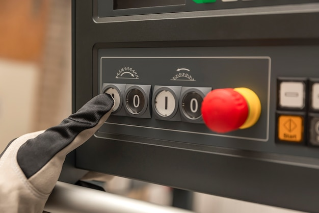 手袋をした手が工場で木工機械の電源ボタンを押すクローズアップ