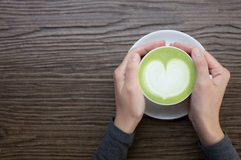 Hand with green tea latte on wood background