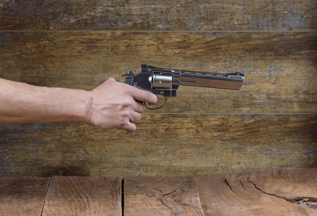 黒の背景に分離された銃を持つ手