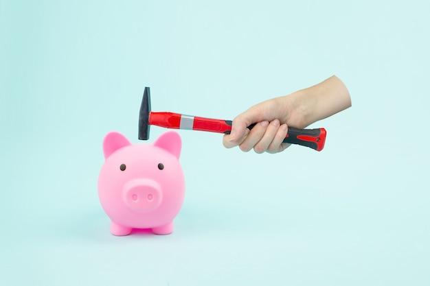 파란색 배경에 망치와 돼지 저금통으로 손. 금융 불안 개념 이미지입니다.