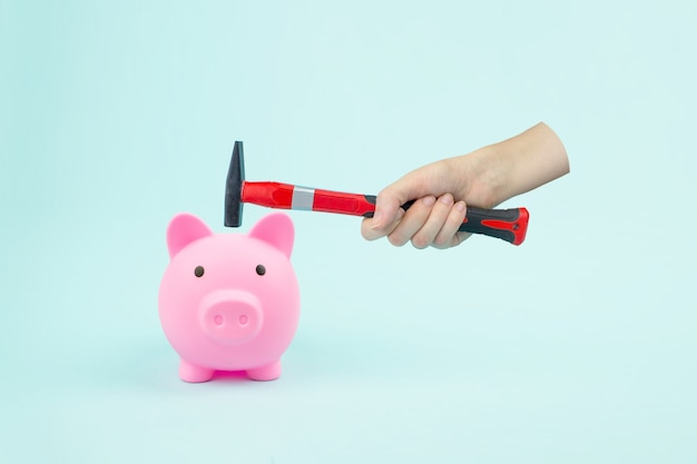 Hand with hammer and piggy bank on blue background. financial insecurity concept image.