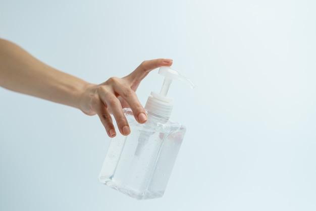 Рука с дезинфицирующим средством для рук в прозрачной бутылке насоса.