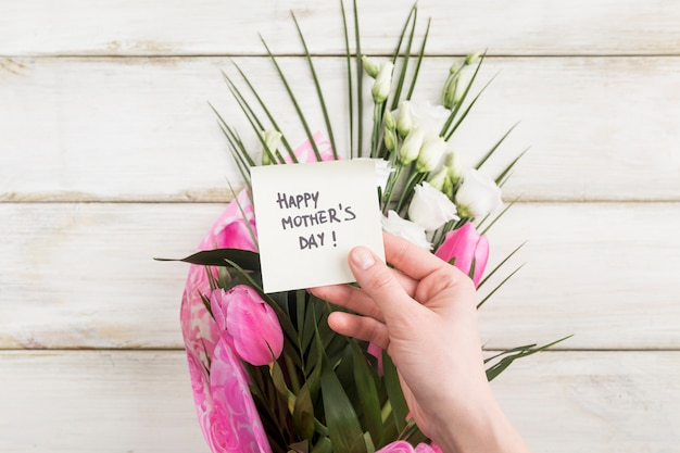 Hand with happy mothers day sticker and bouquet