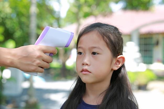 遊び場に入る前にアジアの小さな子供の額を測定する赤外線温度計を手に