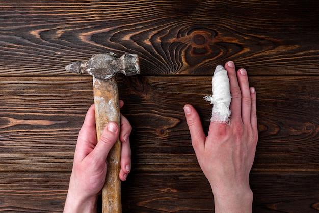 Рука с поврежденным пальцем держит молоток на темном деревянном столе.