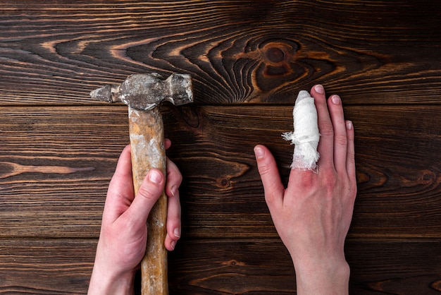 Hand with injured finger is holding a hammer on dark wooden table.