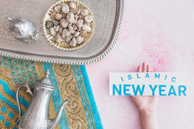 Рука с исламской новогодней бумагой и набором чая на подносе