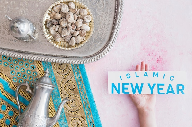 Hand with islamic new year paper and tea set on tray
