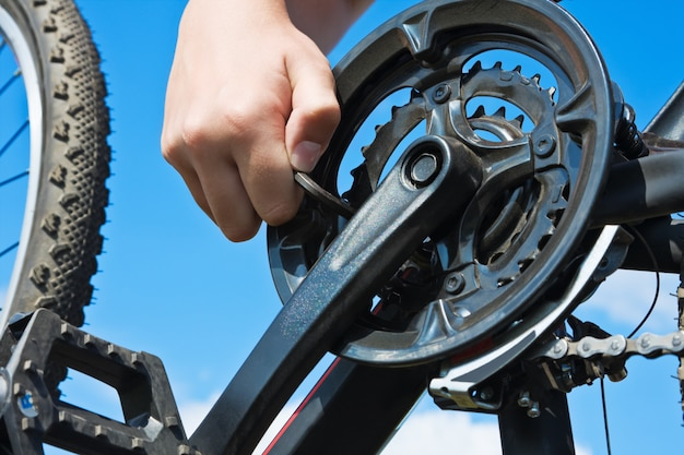 Рука с ключом ремонтирует велосипед