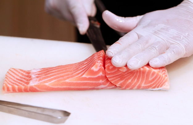 Hand with knife cuts salmon fish.raw fish on cooking board. chef prepares raw fish for jap