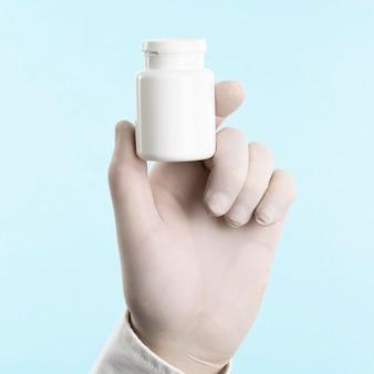 약 병을 들고 라텍스 장갑과 손