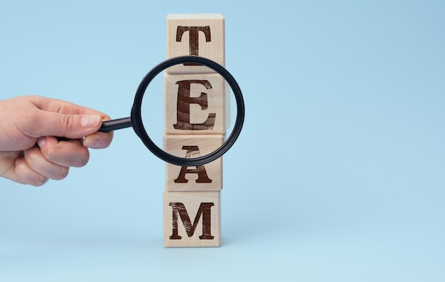 Hand with a magnifying glass on a blue surface. the concept of recruiting and finding talented employees. team building