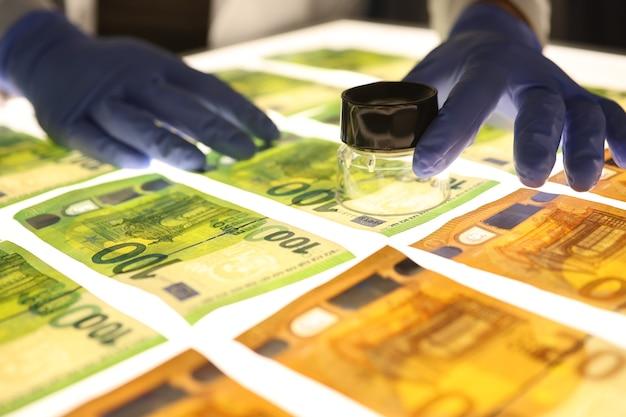 Рука с увеличительным стеклом проверяет подлинность концепции поддельных денег денег