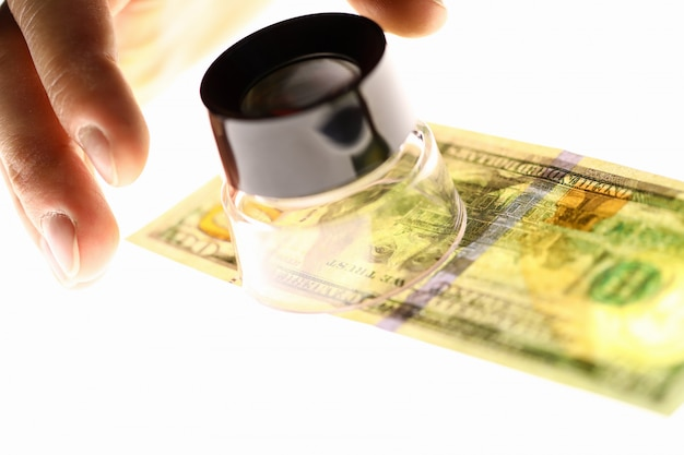 Hand with magnifying glass and dollars, money check