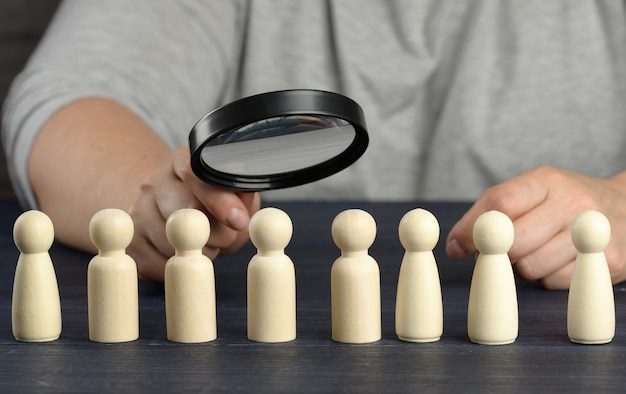 A hand with a magnifying glass examines unique and talented wooden men in the crowd. employee search concept, career growth, layoffs and hiring