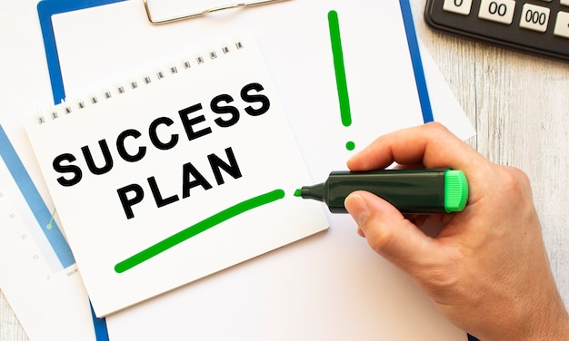 A hand with a marker writes the text success plan in a notebook on the desktop. view from above. business concept.