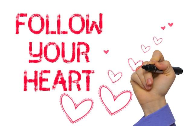 マーカーを書いた手:あなたの心に従ってください。白い背景に