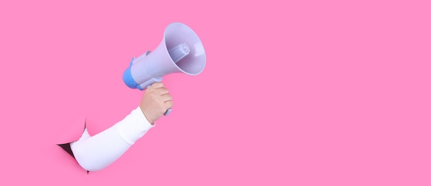 Рука с мегафоном смотрит на розовом фоне