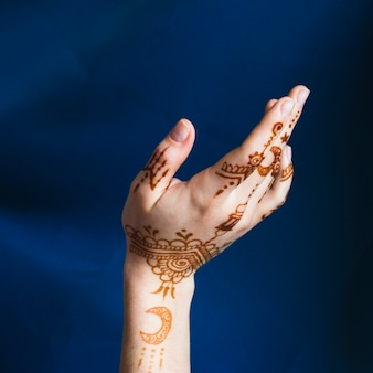 Hand with mehndi near blue textile