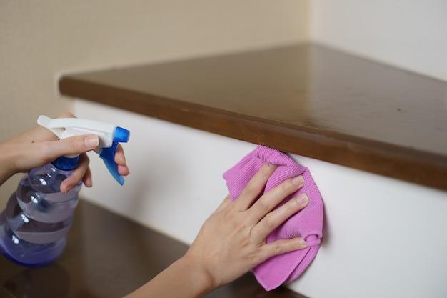 自宅で階段を掃除するマイクロファイバークロスと洗剤スプレーを手に