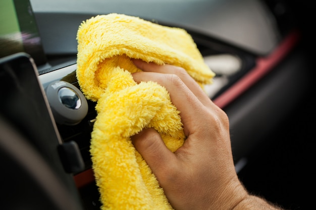 Hand with microfiber cloth cleaning car interior