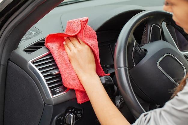 Рука с салфеткой из микрофибры для чистки интерьер современного автомобиля.